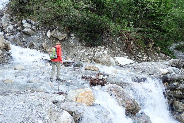 Maaike steekt een rivier over onderweg naar de Tappenkarsee